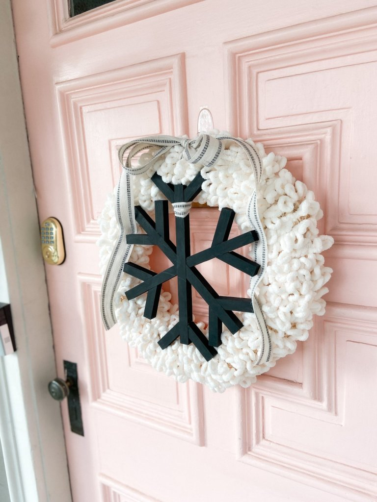 DIY Winter Wood and Yarn Snowflake Wreath. Celebrate winter with an easy yarn-wrapped wreath featuring a handmade giant snowflake!