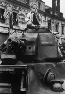 Un bambino siede in cima ad un carro armato durante il discorso di Charles de Gaulle's dopo la liberazione di Parigi da parte delle forze alleate. La foto venne scattata da Robert Capa il 25 agosto 1944.