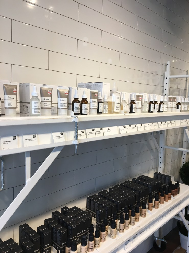 A shelf full of The Ordinary products and foundations