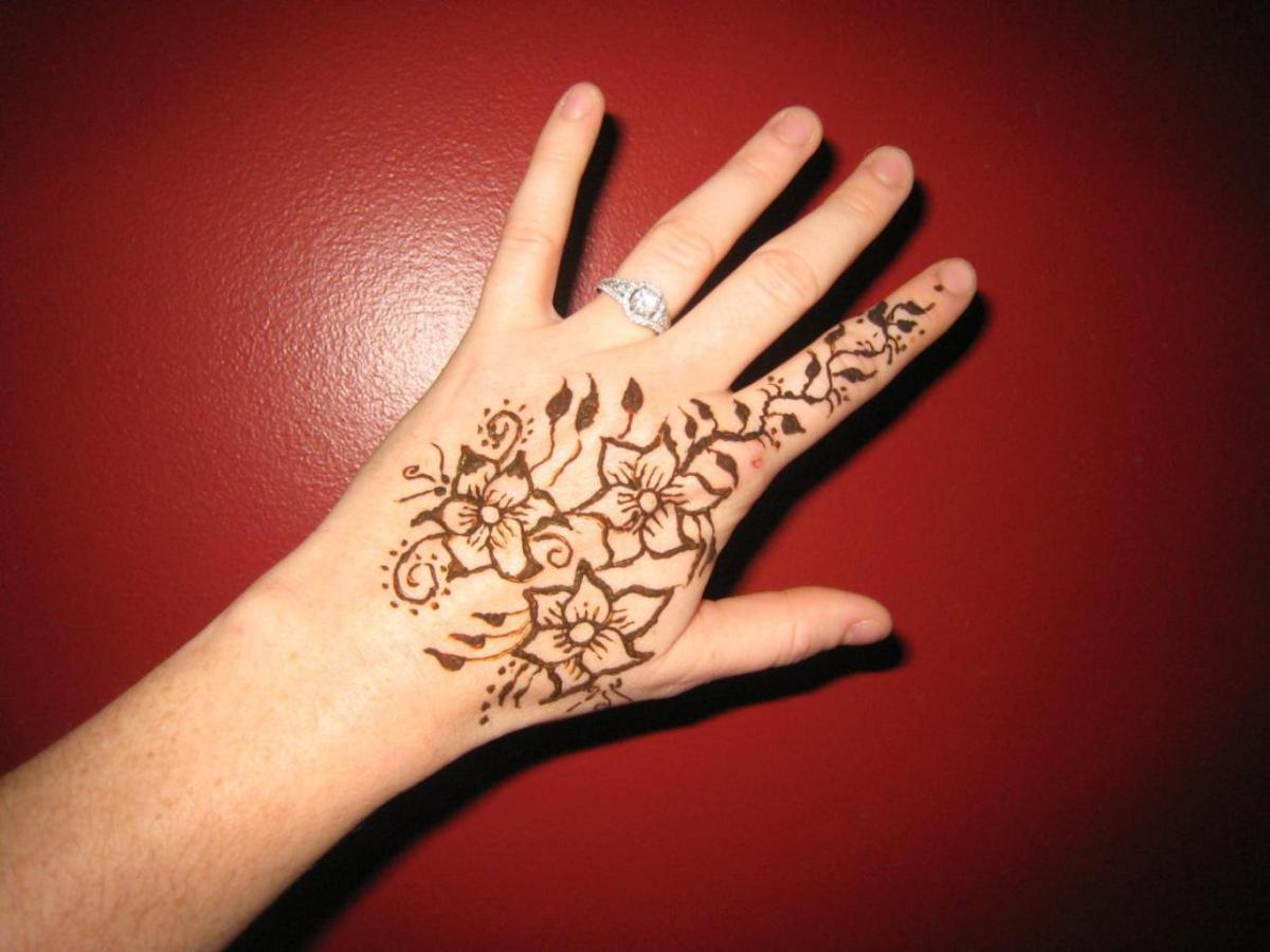 Floral henna tattoo on left hands for women