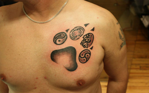 Wolf paw print tattoo on men righ shoulder