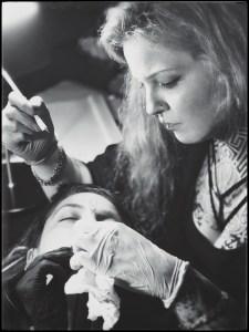 Svartvitt fotografi av Habba Nero handstickande hakan på liggande klient.