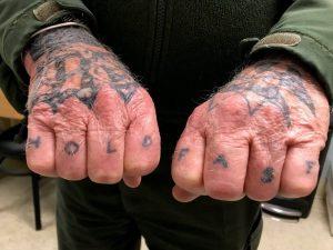 Färgfoto på två framhållna händer, med texten Hold Fast tatuerad på fingrarna.