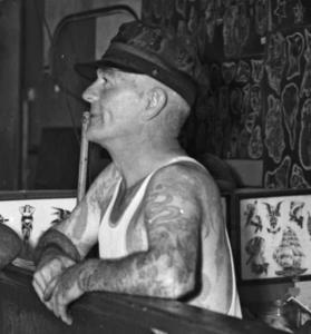 Svartvitt porträttfoto av August Cap Coleman. Rakat huvud, klädd i vegamössa. Tatuerade armar.