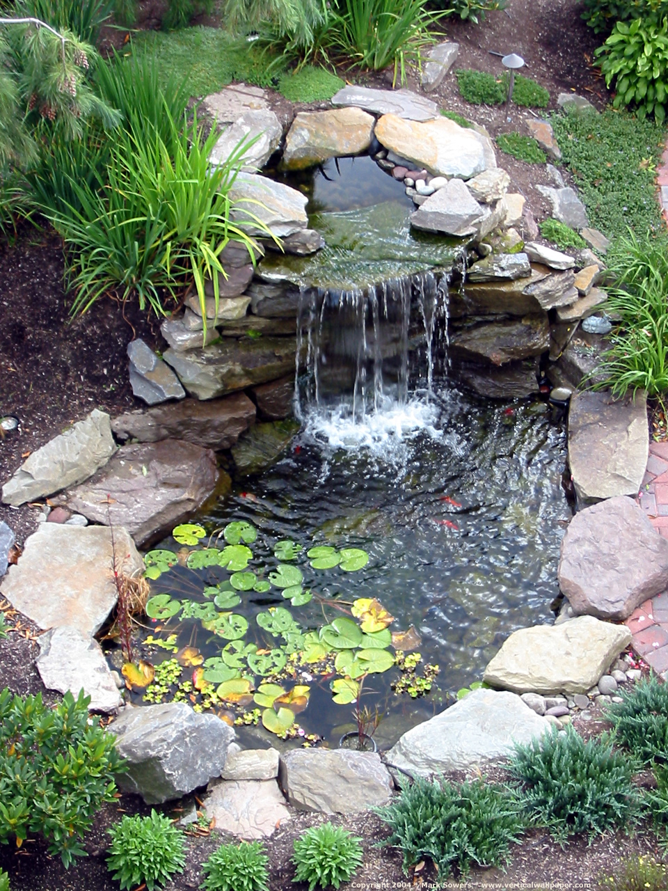 Appealing Small Backyard Waterfall On Fish Pond With Stones Surround for Small Backyard Waterfall Ideas