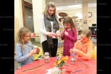 Melia Britton (left) and Chloe Britton (right) work on their crafts while Library Page Kirsten Schultz helps Noelle Daum.