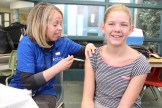 TPS Grade 7 student Lindsay McWhirter gets her vaccination from Nancy Warding, RN.