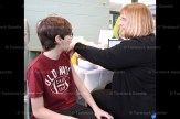 Michael Ropp, 12, gets his shot from Julia Holmes, RN.
