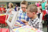 Grade 3 student Hayden McCann (left) shows a book kit to his brother, Dylan, a Senior Kindergarten student at the Annual Book Fair at Tavistock Public School last Wednesday evening.
