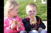 Siblings Leah Weicker, 4, and Aden Weicker, 3, get a taste of the firemen's hot dogs at the School Open House, May 4th.