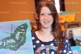 Tori Jantzi shows a butterfly painting she did for the Art Show Saturday.
