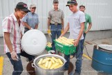 Andrew McPherson (left) and Troy Wilson check the corn cooking at the 41st annual Cattlemen's Association Beef BBQ held last Thursday, August 11th. Behind are Dwight Zehr, Bill Dibble and Clayton Granville.
