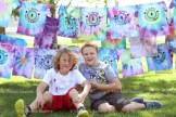 Blake Stere (left) and his cousin Alex Michiels, both 9, relax in front of Camp Alliwannado tie-dyed t-shirts following a game in the park.