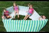 Clockwise, from the left, Tessa Burdett, Calleigh Bontaine, twins Macy and Summer Kollman, and Tessa Gerber play in a lycra tube during play time at Camp Alliwannado.