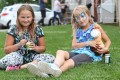 Madison a, 10, and Jessica Edmondson, 11, have a picnic on the lawn at the fair.