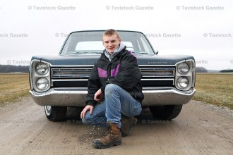 Dwight Herlick, 16, poses with his great grandfather's 1968 Plymouth Fury I which Dwight restored to working order last year.