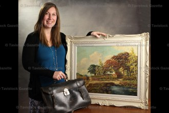 Tavistock Public School music teacher Sara Gallant poses with Miss Ida Kollman's leather music bag and framed oil painting. Miss Kollman, Sara's late great aunt, received the painting when she retired from teaching at Tavistock School in December of 1967.
