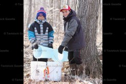 Brenneman brothers Morgan (left) and Nathan collect sap in pails out in the family's woodlot.