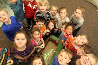 Kindergarten students gather around their leprechaun trap set up to capture the two little creatures who left their footprints there.