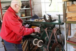 Heinz Riedel demonstrates the antique shoe machine once owned by Charlie Miles during his garage sale Saturday.