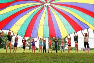 TPS Play Day parachute game participants (from the lefT0 Max Stegmann, Callie Brenneman, Lily Hauss, Noah Zehr, Sadie Breyer, Ella Skinner, Liam Odette, Cohen Smith, Jett Stigter, Lyric Brighton, Emma Weitzel, Jenna McWhirter, Danielle Coddington.
