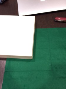 The borders of box are about a quarter of an inch  thick.  Trim it down slowly   until it fits.