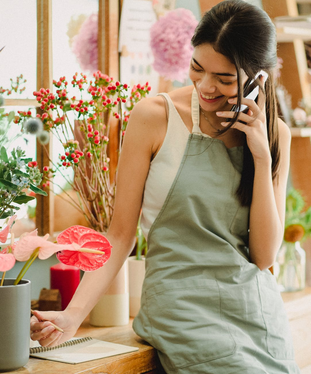 smiling female florist talking on phone in floristry shop