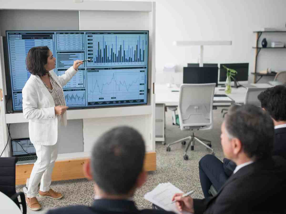 woman in white suit discussing stock market data to her colleagues