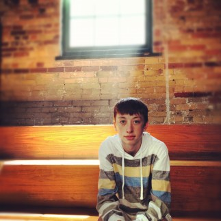My brother, Jacob, sitting on a bench in a chocolate shop in the distillery district in Toronto, ONT