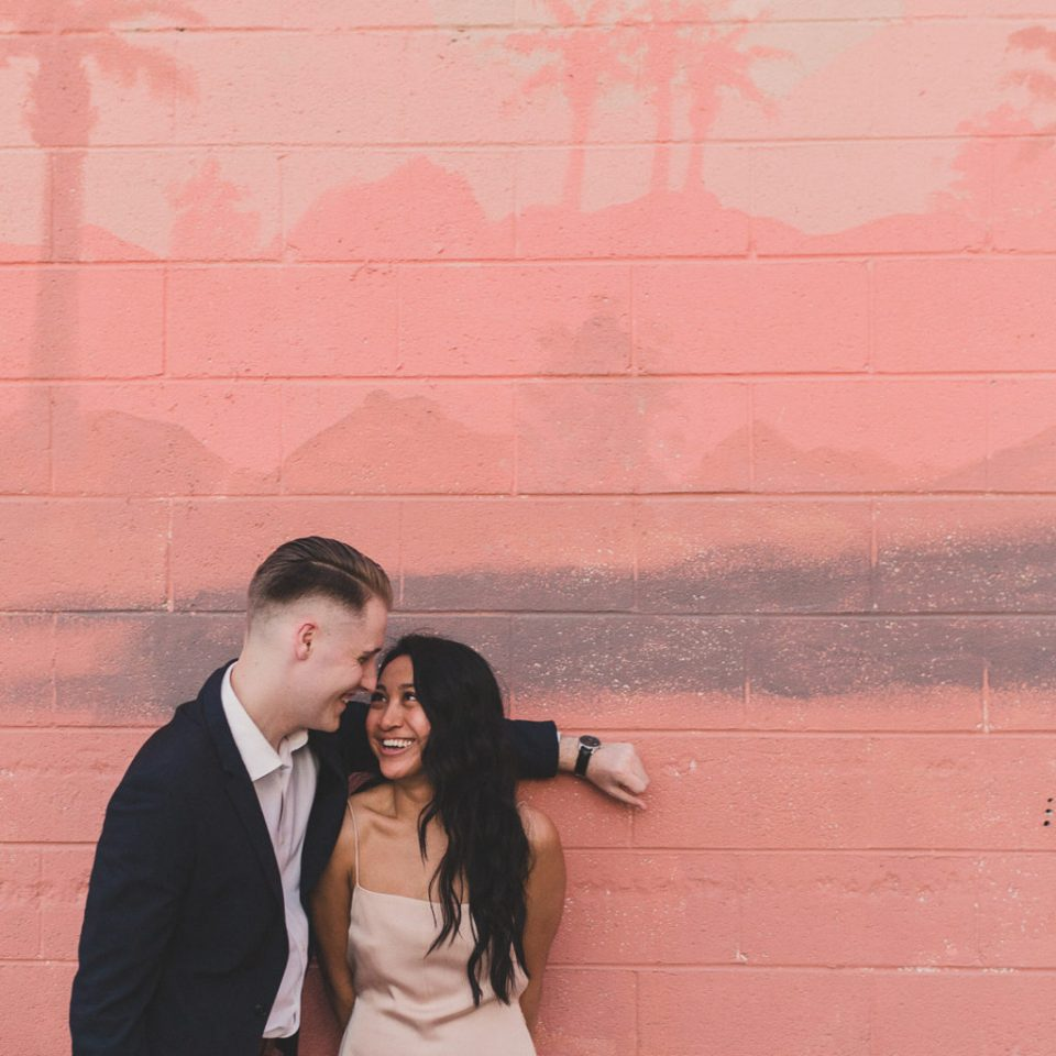 Taylor Made Photography captures engagement portraits by pink mural