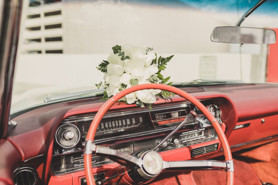 bride's white bouquet sits on dashboard of Cadillac