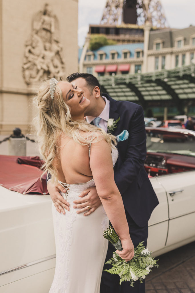 groom kisses bride by Las Vegas monuments on wedding day
