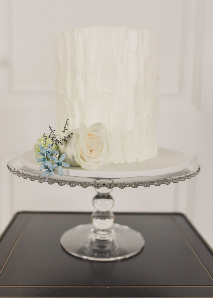 one tiered wedding cake with ivory flowers on silver stand photographed by Taylor Made Photography