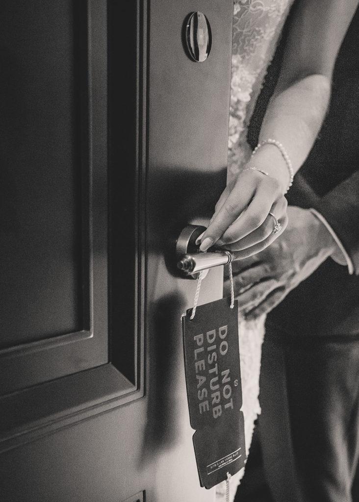 "bride and groom place ""do not disturb"" sign on hotel room door"