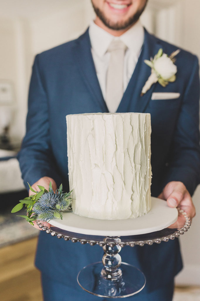 Taylor Made Photography captures groom holding tiered wedding cake