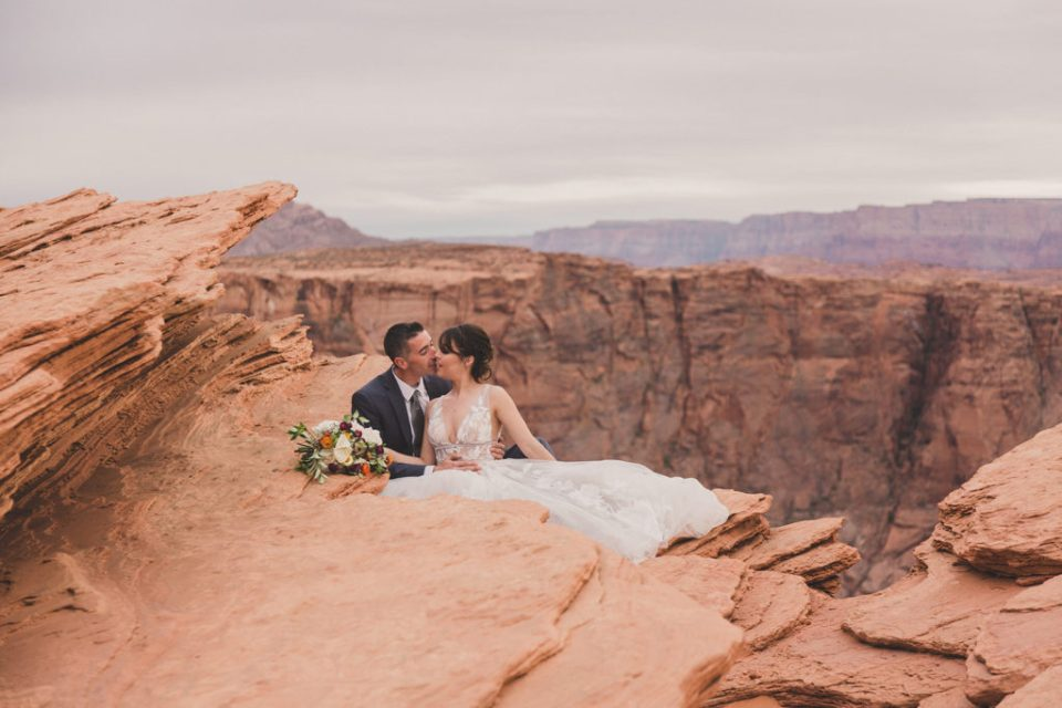 bride and groom sit together during elopement in Horseshoe Bend