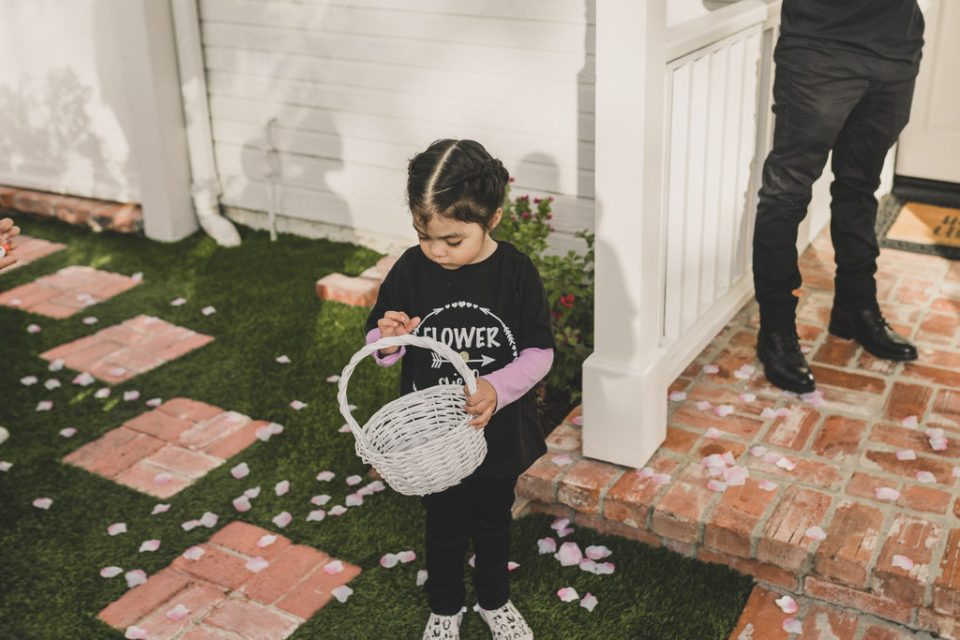 flower girl plays with basket of petals photographed by Taylor Made Photography