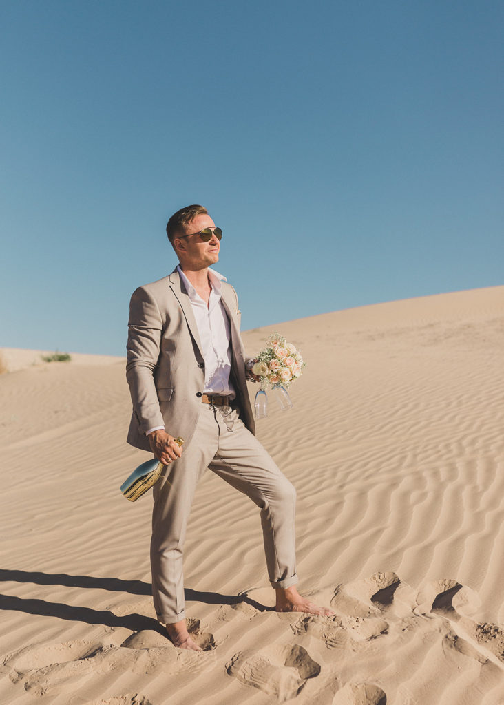 groom poses in sand photographed by Taylor Made Photography