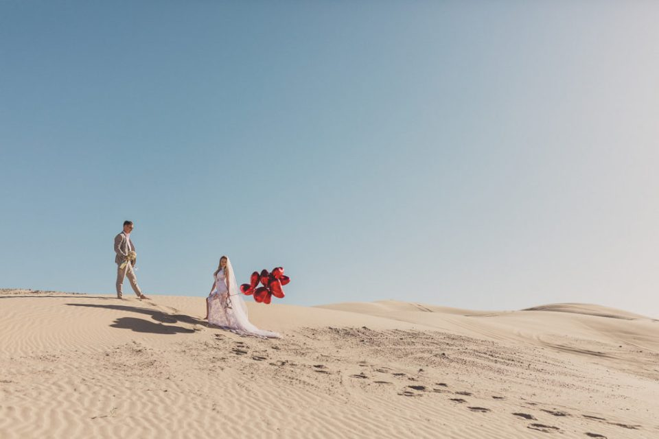newlyweds pose on sand dunes in Las Vegas for Taylor Made Photography