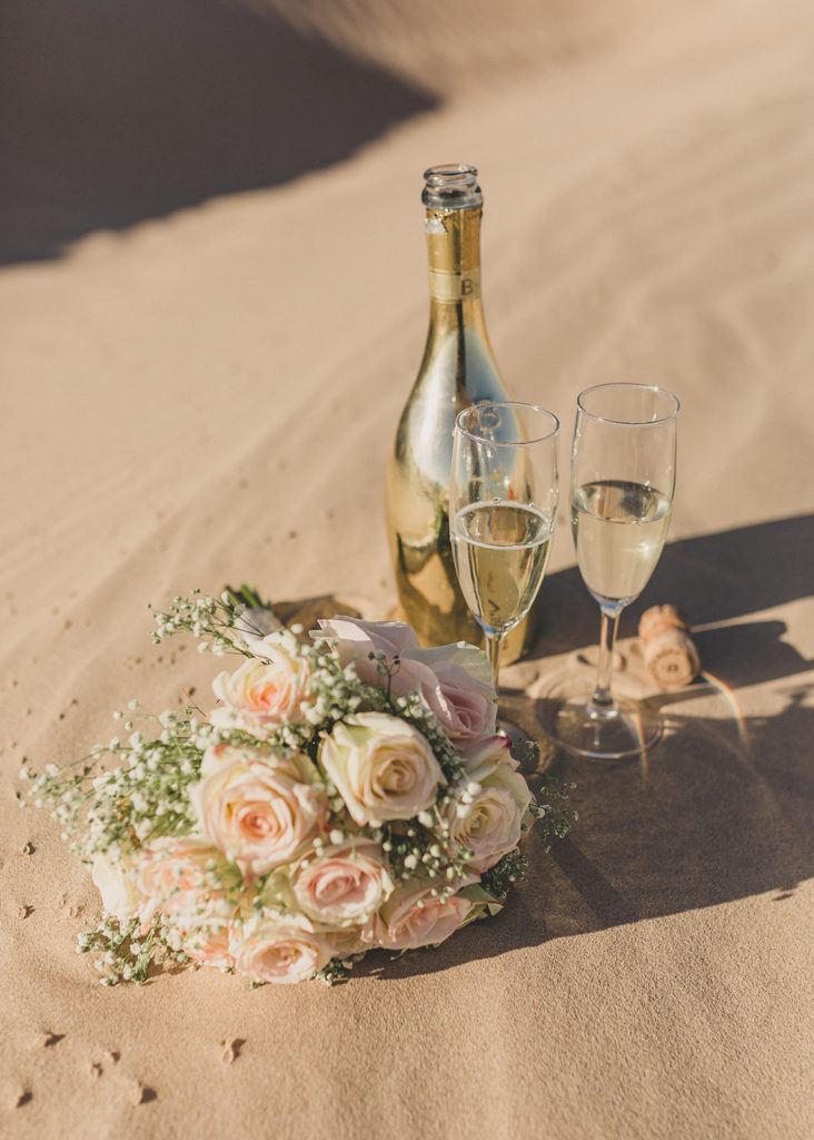champagne and bridal bouquet on sand dunes in Las Vegas with Taylor Made Photography