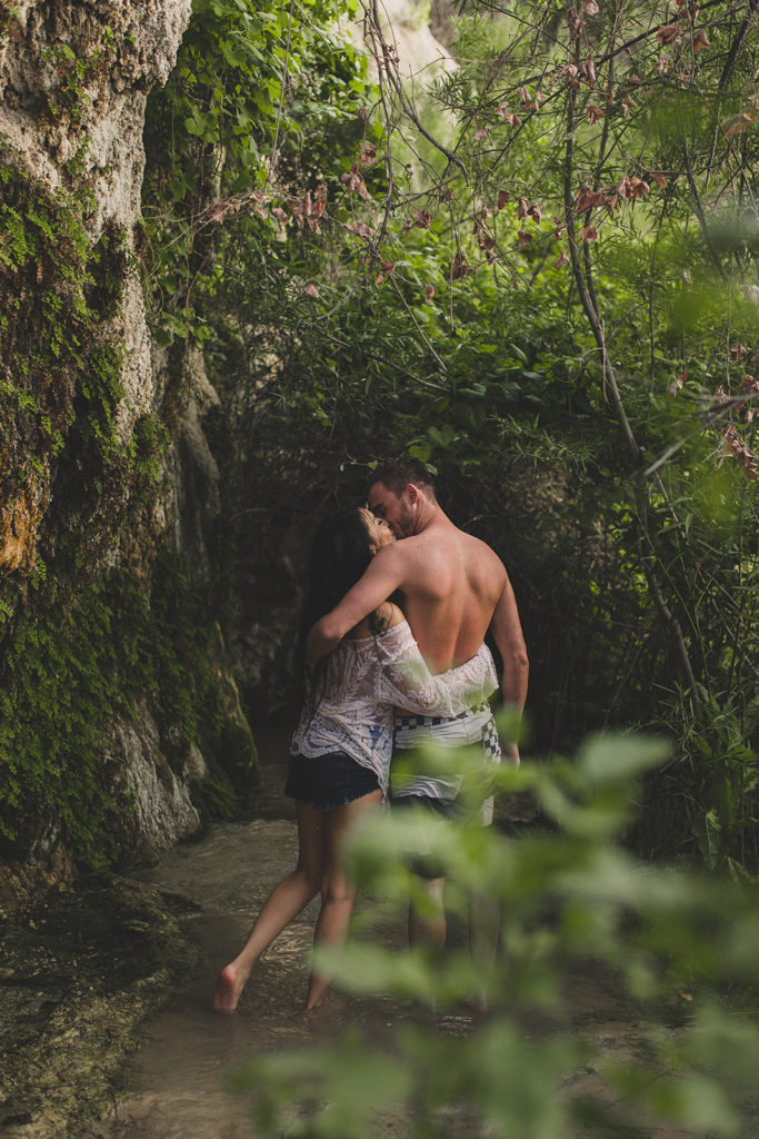Taylor Made Photography photographs couple kissing in foliage at Little Jamaica