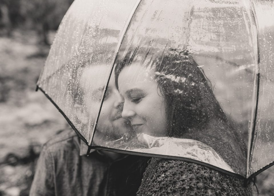 couple embraces under umbrella during rainy engagement session photographed by Taylor Made Photography