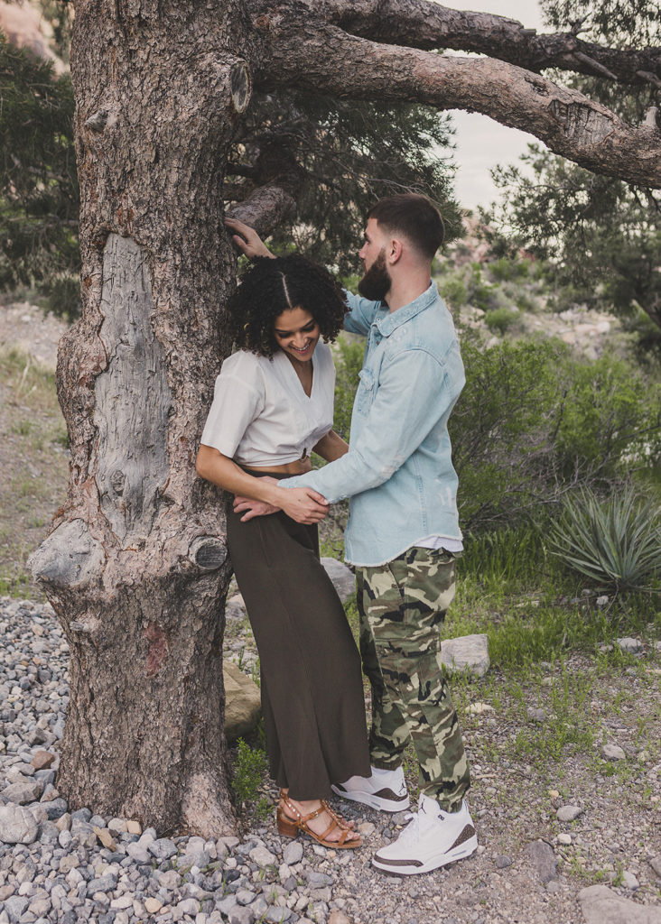 bride and groom to be pose by tree in Las Vegas park with Taylor Made Photography