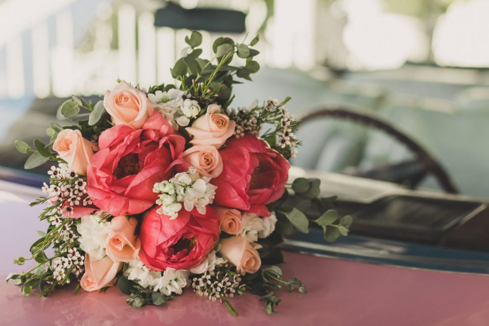 bride's colorful bouquet rests on pink Cadillac at Little White Way
