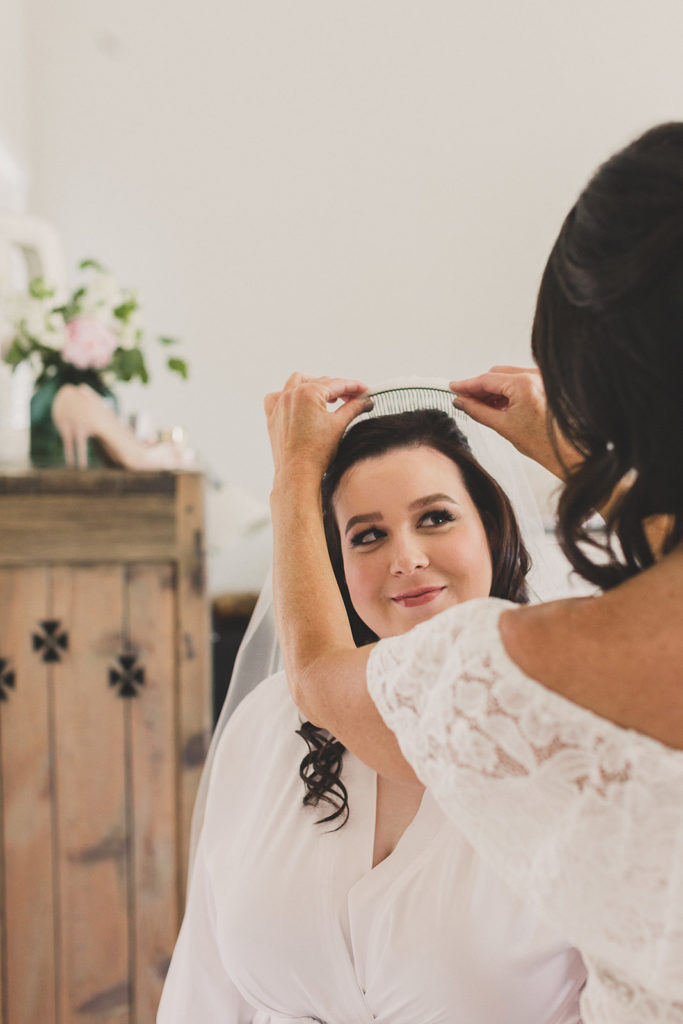 bride has veil placed by family photographed by Taylor Made Photography