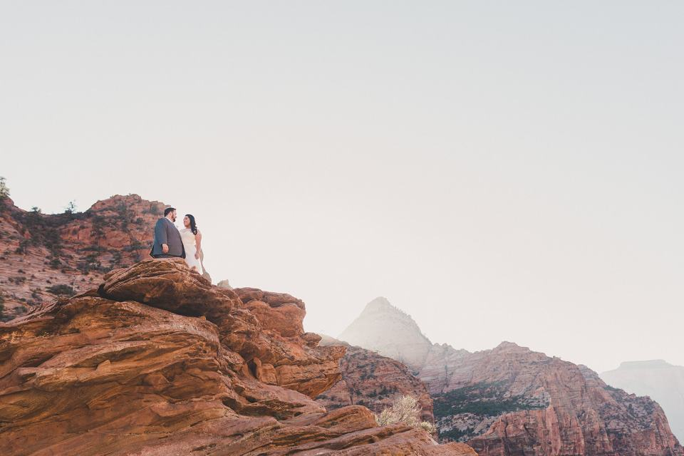 bride and groom stand on ledge in Zion National park with Taylor Made Photography