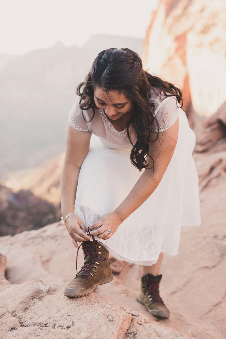 bride puts on hiking boots after wedding ceremony photographed by Taylor Made Photography