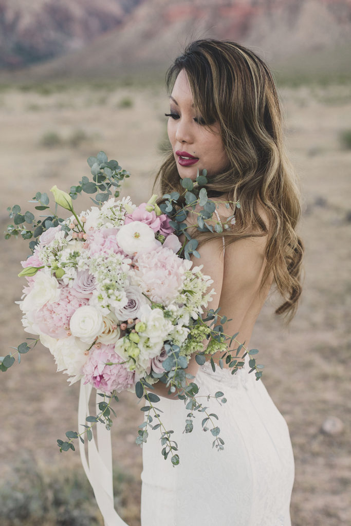 bride looks at pastel bouquet photographed by Taylor Made Photography