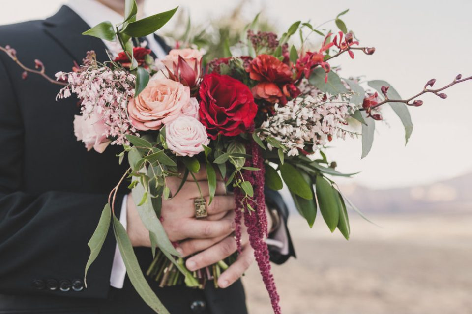 groom holds bride's bouquet with red roses