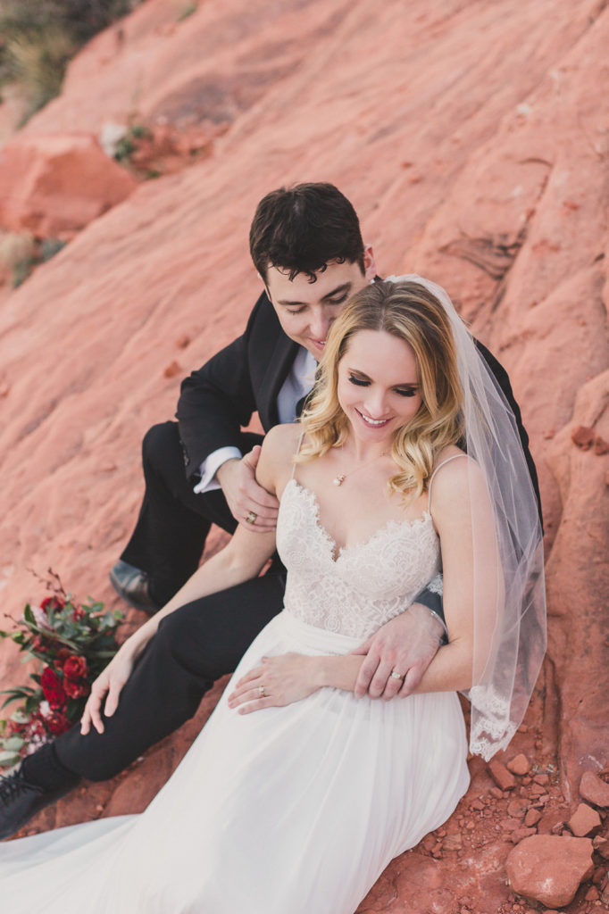 bride and groom sit on red rocks at Red Rock Canyon in Las Vegas